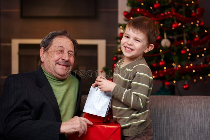 Menino novo que dá o presente de Natal ao avô fotografia de stock royalty free