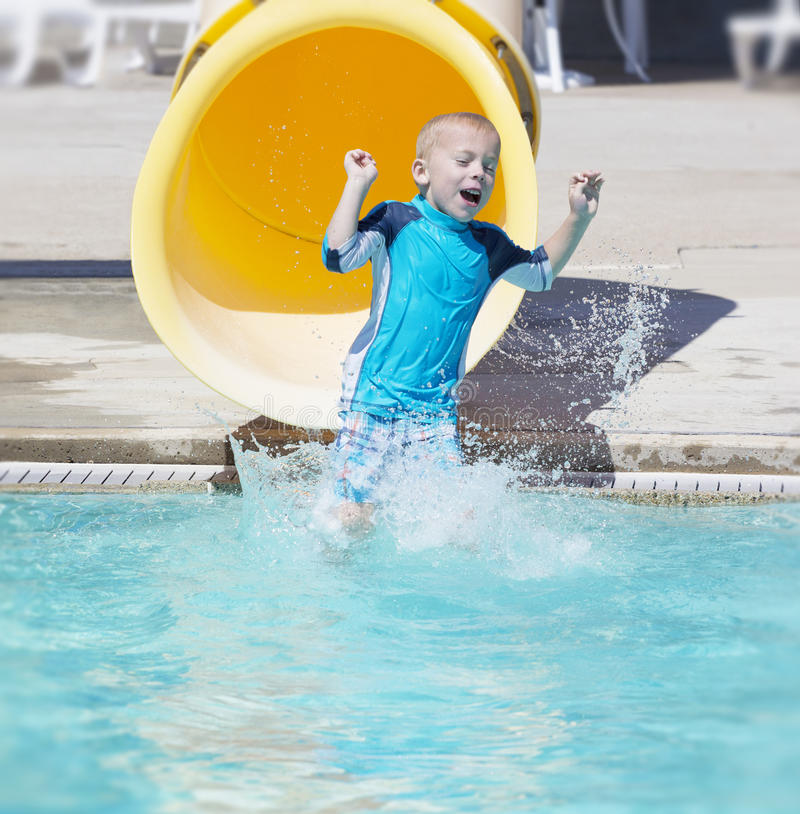 Menino novo que desliza fora de uma corrediça de água amarela imagens de stock