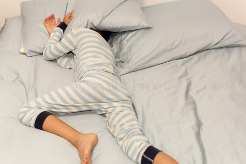 Menino novo que dorme na cama com sua cabeça sob o descanso em casa fotos de stock