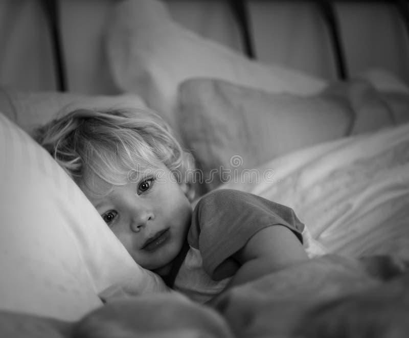 Menino novo que encontra-se em descansos na cama imagem de stock royalty free