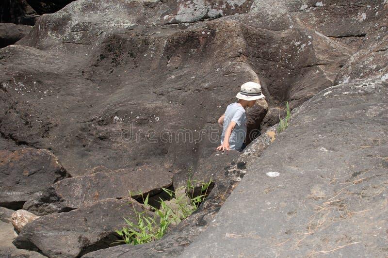 Menino novo que escala entre rochas fotos de stock royalty free
