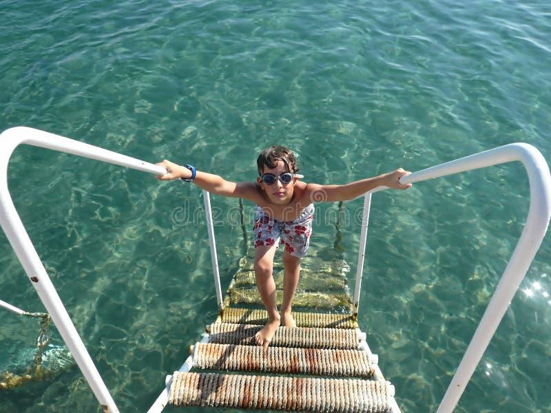 Menino novo que escala a escada no mar fotografia de stock