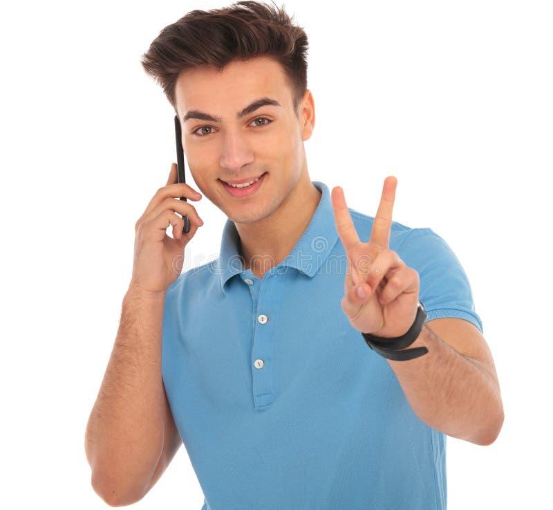 Menino novo que fala no móbil e que mostra o sinal da vitória fotografia de stock
