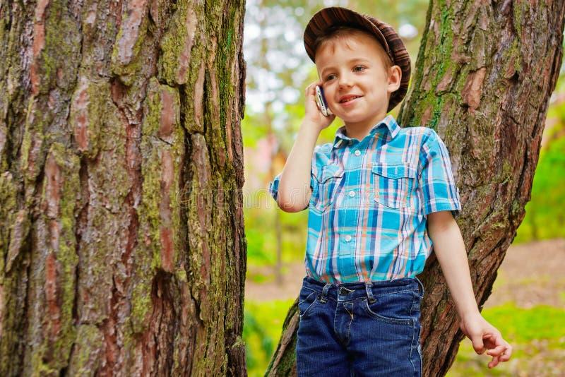 Menino novo que fala no telefone celular foto de stock
