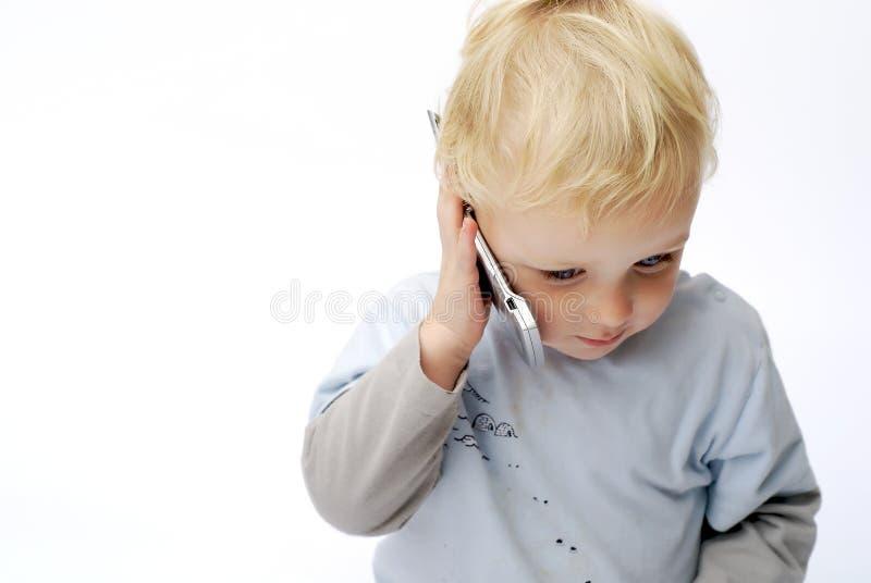 Menino novo que fala no telefone móvel fotos de stock royalty free