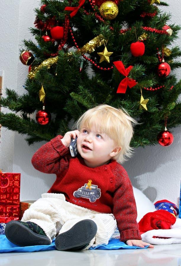 Menino novo que fala no telefone móvel sob uma árvore de Natal. fotografia de stock royalty free
