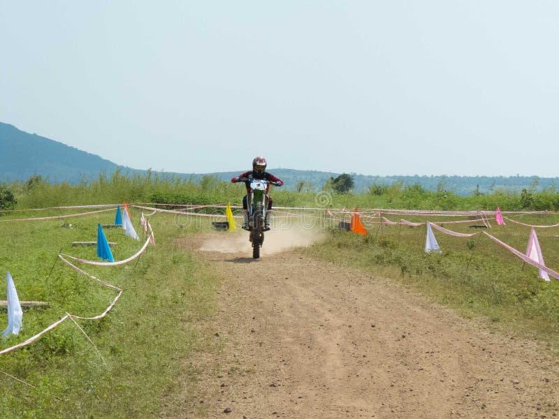 Menino novo que faz o conluio do wheelie no evento do motocross fotografia de stock royalty free