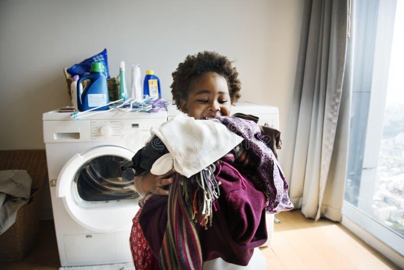 Menino novo que faz trabalhos domésticos em casa foto de stock