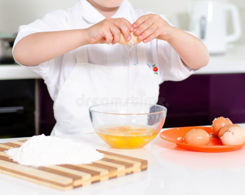Menino novo que ganha para ser um cozinheiro chefe foto de stock