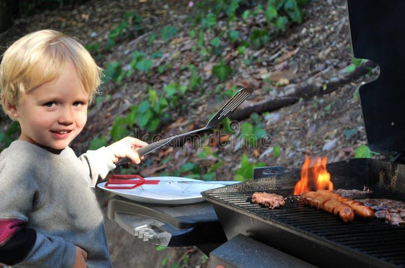 Download Menino Novo Que Grelha O Alimento Foto de Stock - Imagem de outdoors, grelhar: 10064128