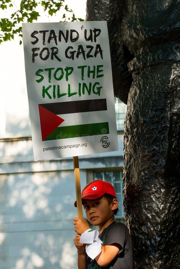 Menino novo que guarda o cartaz em Gaza: Pare a reunião do massacre em Whitehall, Londres, Reino Unido fotografia de stock