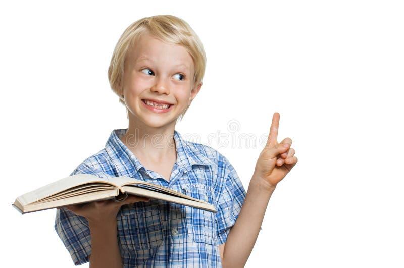 Menino novo que guarda o livro e apontar imagens de stock royalty free