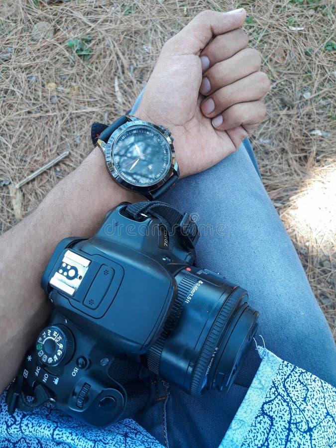 Menino novo que guarda uma câmera de Digitas SLR e que mostra o relógio foto de stock royalty free