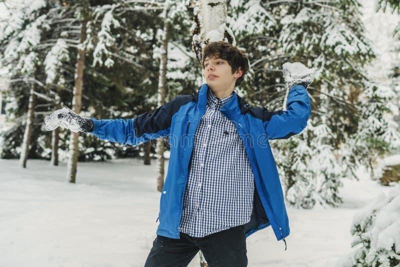 Menino novo que joga a bola de neve e as outras atividades do inverno em um dia nevado no parque f imagens de stock