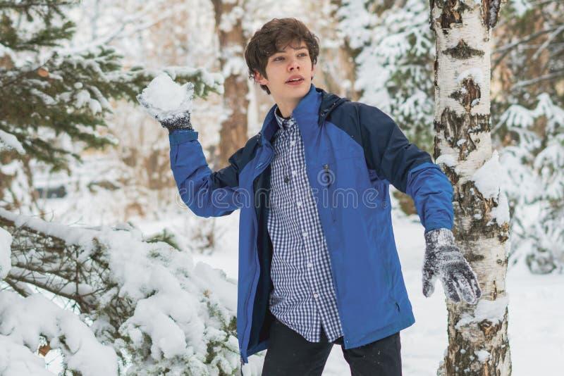 Menino novo que joga a bola de neve e as outras atividades do inverno em um dia nevado no parque f fotografia de stock royalty free