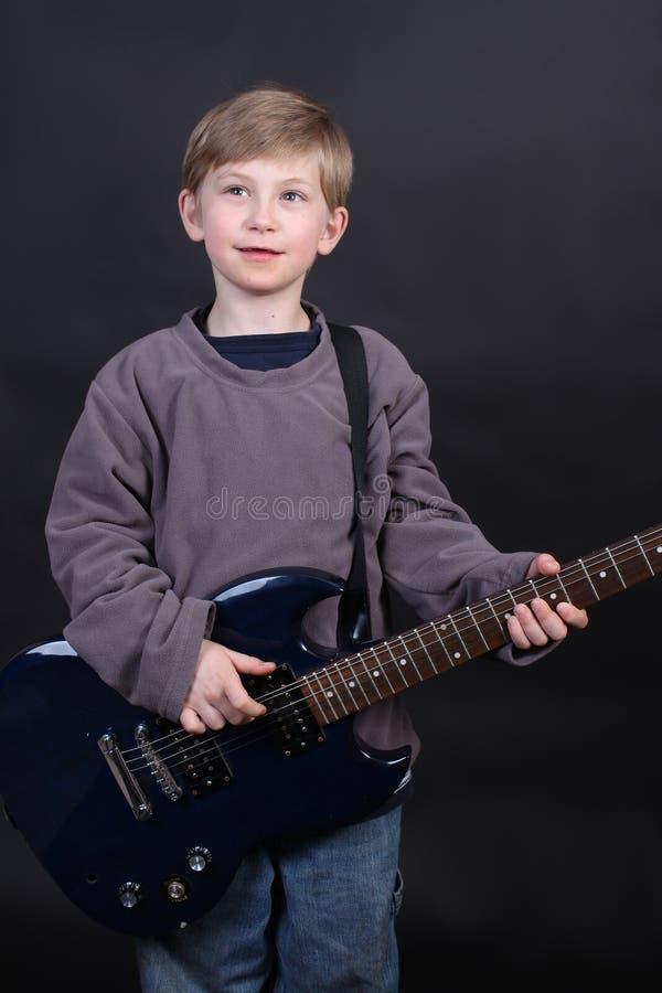 Menino novo que joga a guitarra fotos de stock royalty free