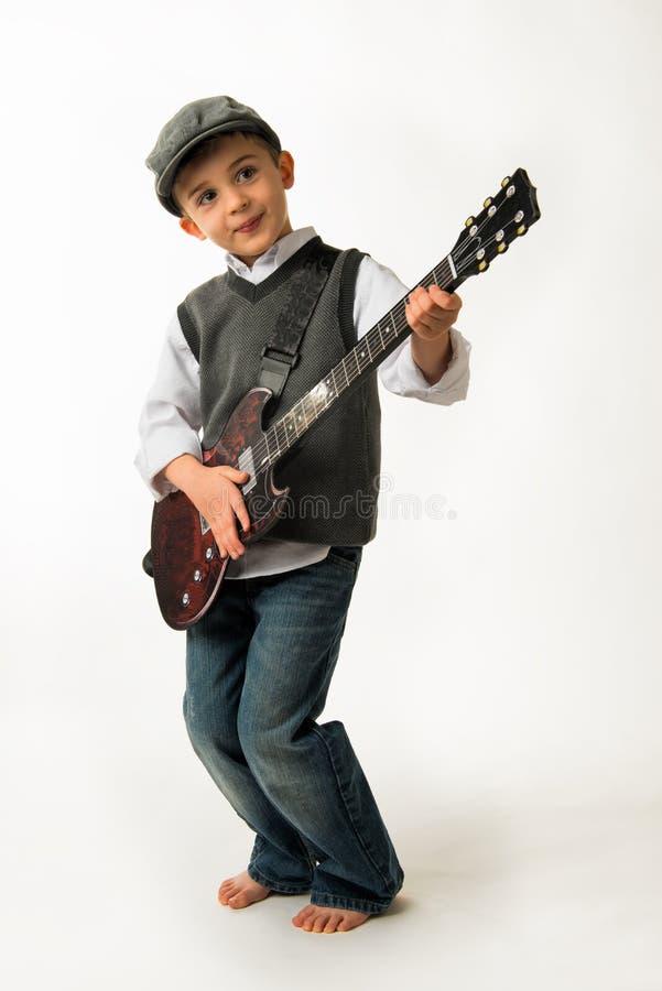 Menino novo que joga a guitarra fotografia de stock