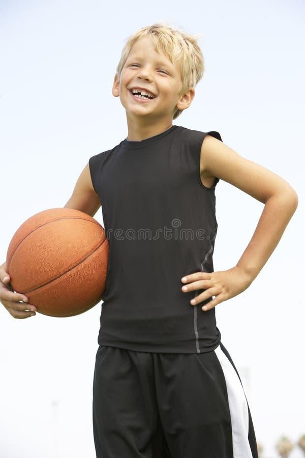 Menino novo que joga o basquetebol fotografia de stock royalty free
