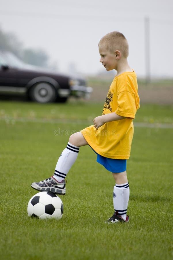 Menino novo que joga o futebol foto de stock