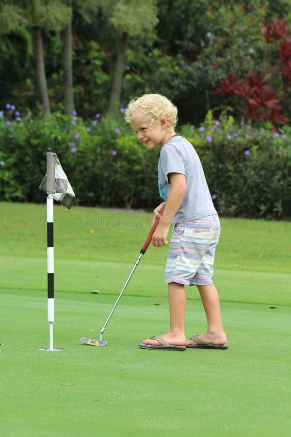 Menino novo que joga o golfe foto de stock royalty free