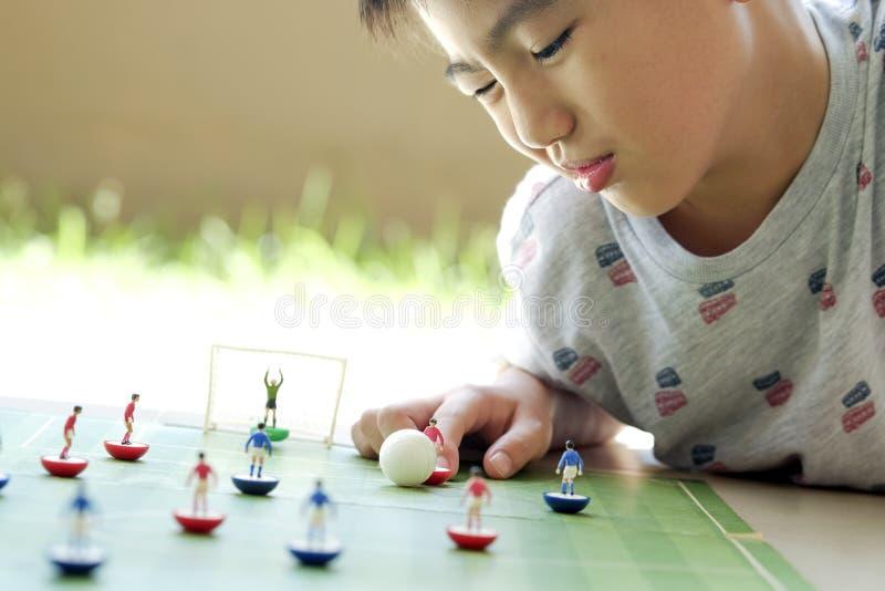 Menino novo que joga o jogo de mesa do futebol da tabela foto de stock