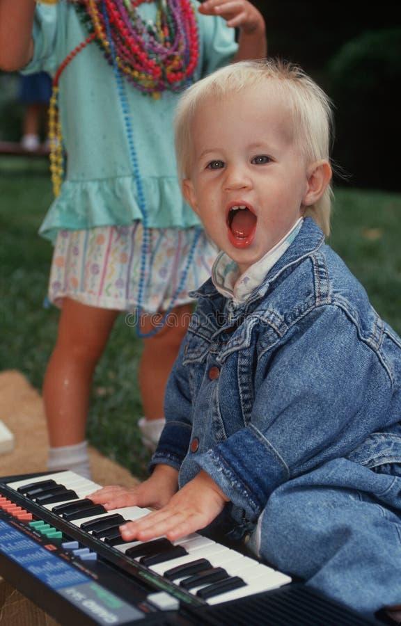 Menino novo que joga o piano do brinquedo imagem de stock