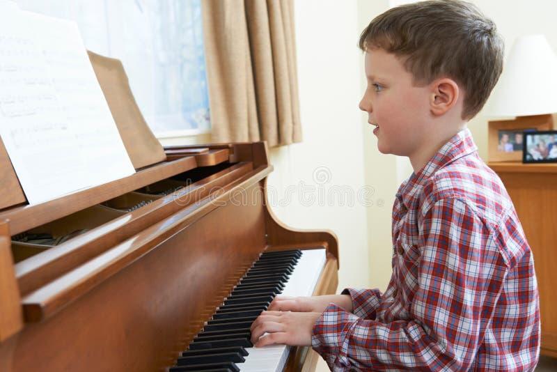 Menino novo que joga o piano em casa foto de stock royalty free