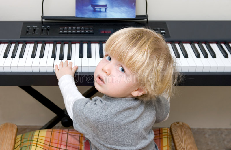 Menino novo que joga o piano ou o teclado fotos de stock