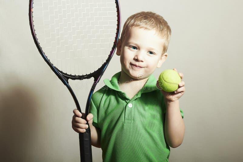 Menino novo que joga o tênis. Crianças do esporte. Criança com raquete e bola de tênis imagens de stock royalty free