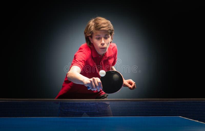 Menino novo que joga o tênis de mesa do pong do sibilo fotos de stock royalty free