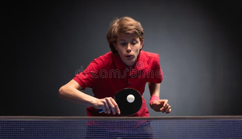 Menino novo que joga o tênis de mesa do pong do sibilo fotografia de stock royalty free