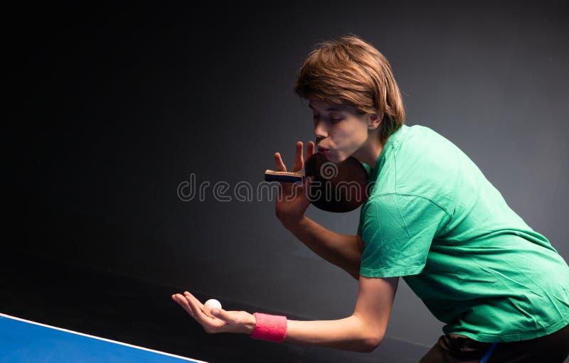 Menino novo que joga o tênis de mesa do pong do sibilo foto de stock