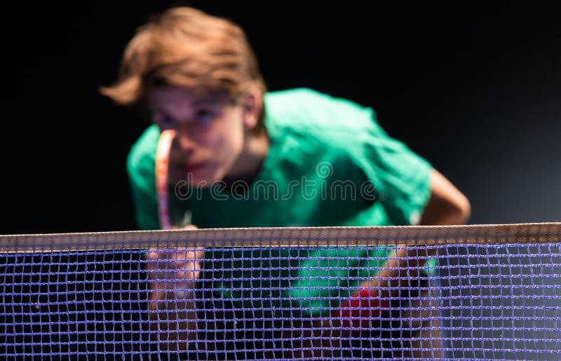 Menino novo que joga o tênis de mesa do pong do sibilo imagens de stock