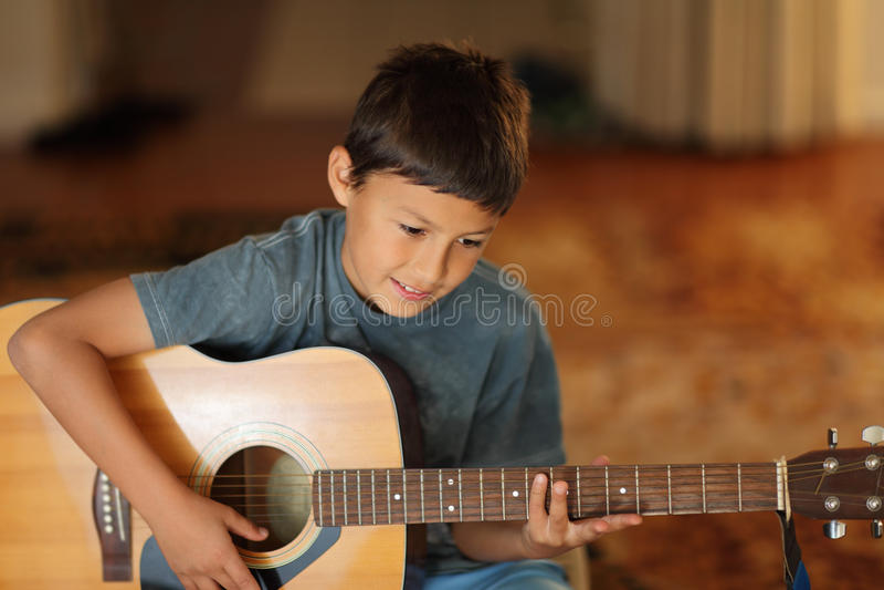 Menino novo que joga uma guitarra fotografia de stock royalty free