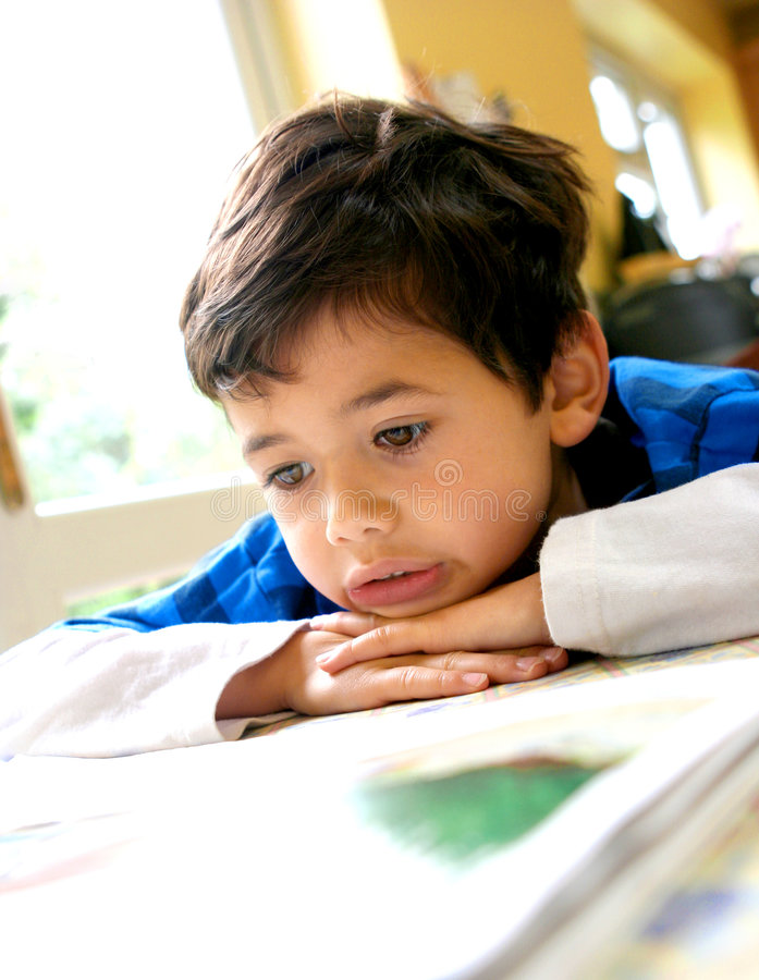 Menino novo que lê um livro. fotografia de stock royalty free
