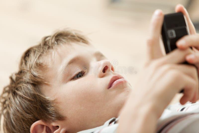 Menino novo que lê uma mensagem de texto em seu móbil fotografia de stock