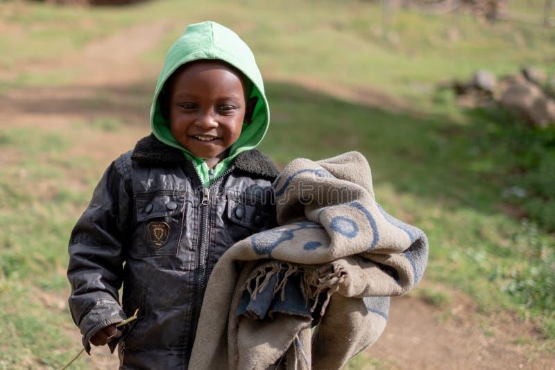 Menino novo que leva uma cobertura em uma vila pequena perto da cidade de Mokhotlong em Lesoto do nordeste, África foto de stock