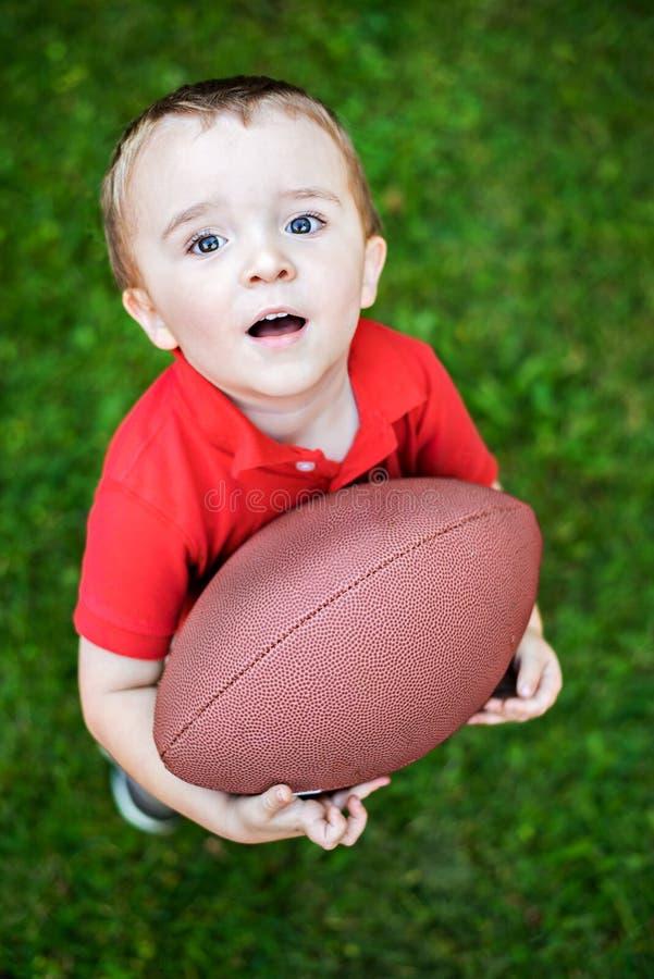 Menino novo que levanta com futebol imagem de stock