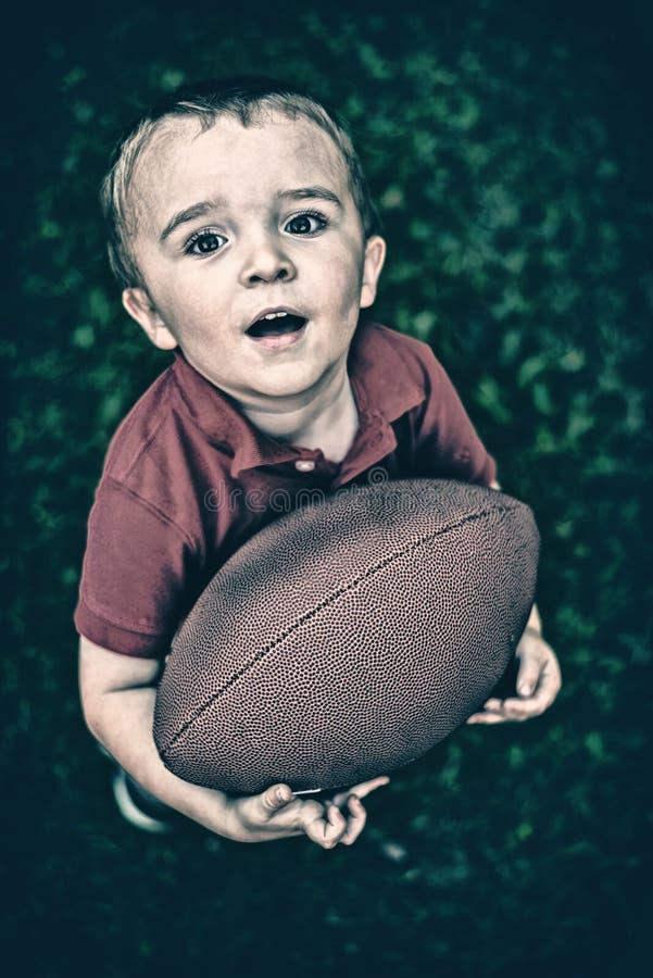 Menino novo que levanta com o futebol - retro fotos de stock royalty free