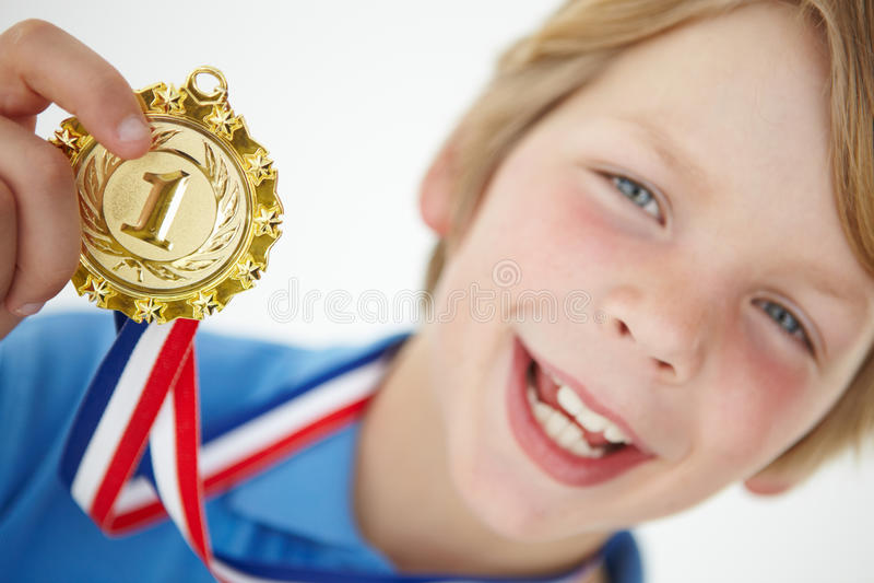 Menino novo que mostra fora a medalha fotografia de stock