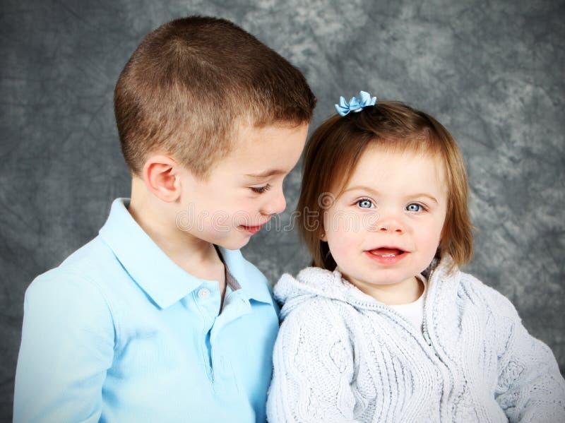 Menino novo que olha adoringly na menina fotografia de stock royalty free