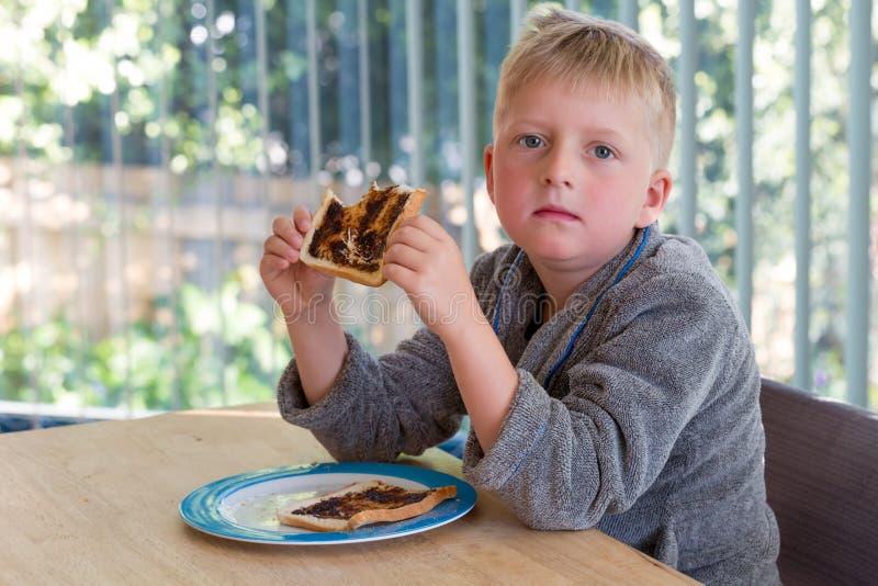 Menino novo que parece cansado a mesa de cozinha que come o brinde para o café da manhã fotografia de stock