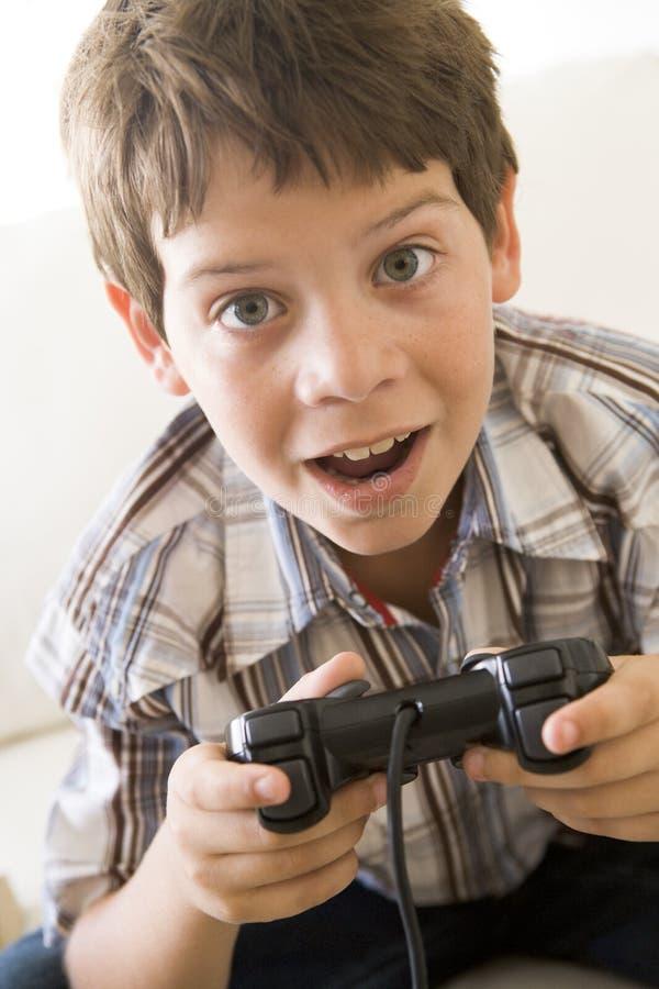 Menino novo que prende o controlador do jogo video fotografia de stock