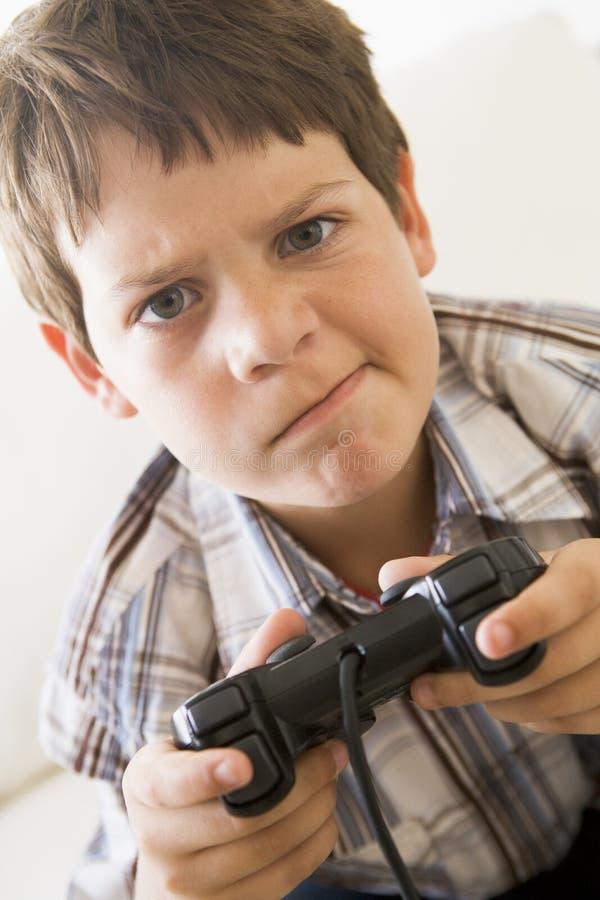 Menino novo que prende o controlador do jogo video imagem de stock royalty free