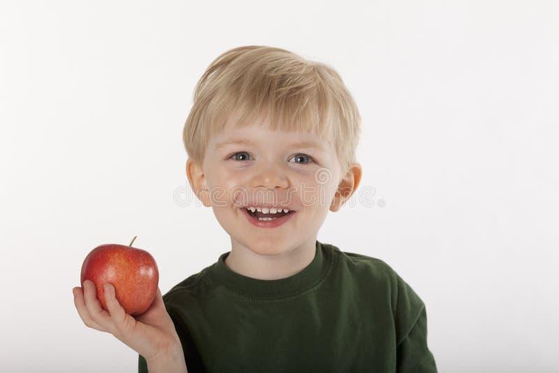 Menino novo que prende um Apple fotografia de stock royalty free