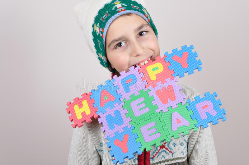Menino novo que realiza em seus dentes um sinal do ano novo feliz imagens de stock