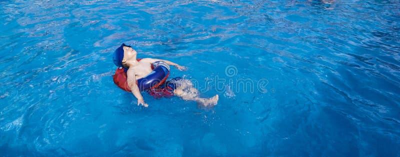 Menino novo que relaxa na piscina foto de stock royalty free