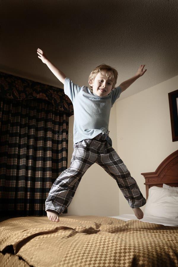 Menino novo que salta na cama imagem de stock royalty free
