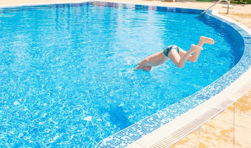 Menino novo que salta na piscina fotografia de stock