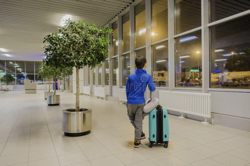Menino novo que senta-se apenas em um corredor do aeroporto em sentir o humor triste fotos de stock